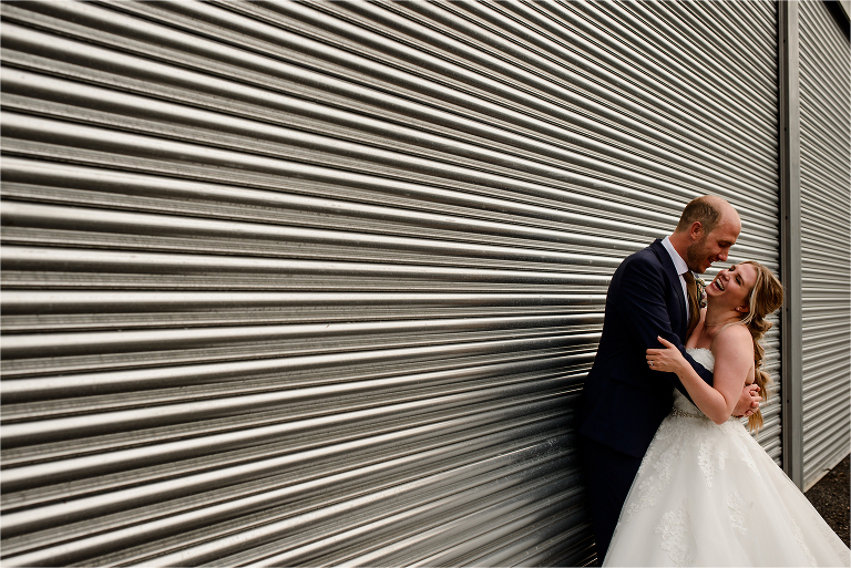 Bride and Groom laughing against a metal shutter