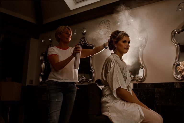 Backlit image on Bride having hairspray put on