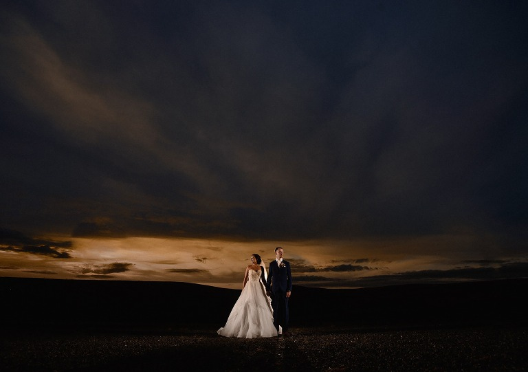 Bride and groom standing in front of a beautiful sky at sunset