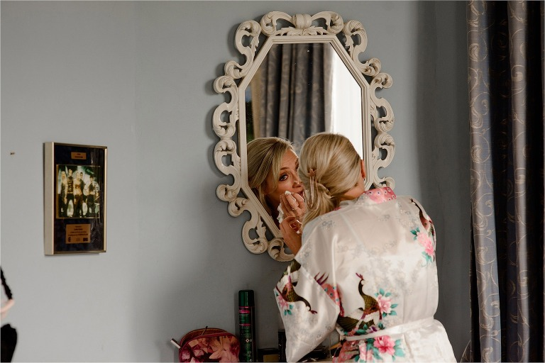 Bride wiping away tears in the mirror
