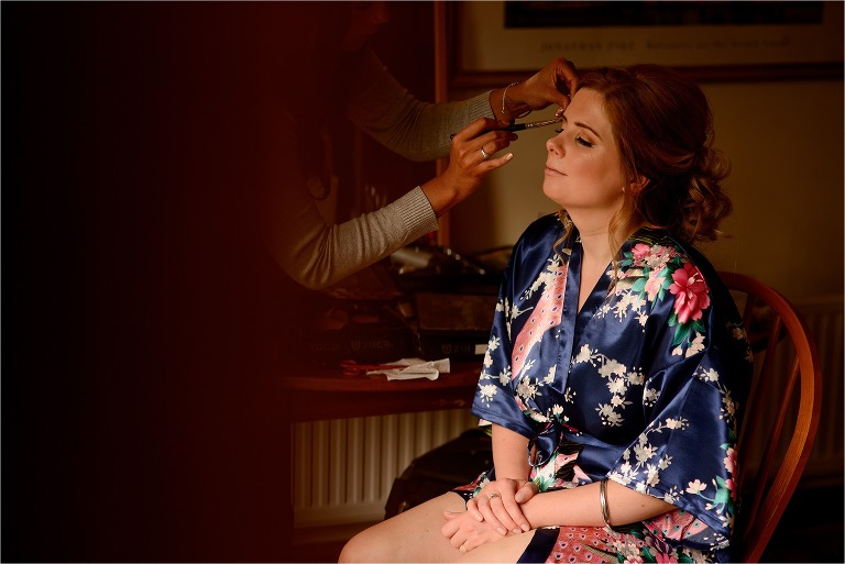 Bridesmaid having her make up done wearing a robe
