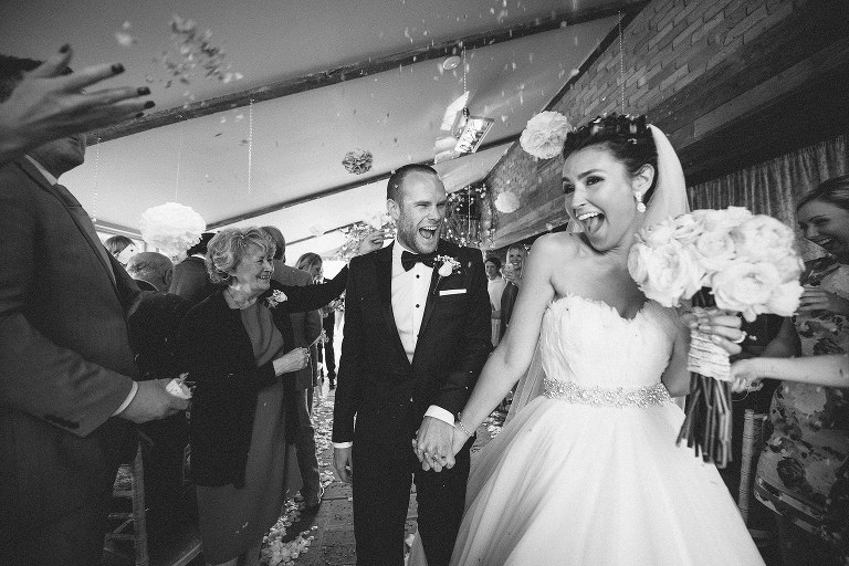 Bride and groom laughing as the walk up the aisle together holding hands.