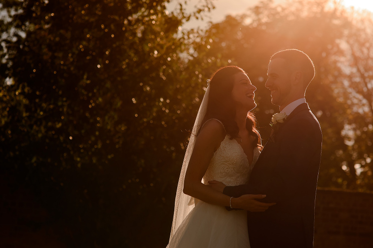 Bride and Groom with light coming through some trees behind them