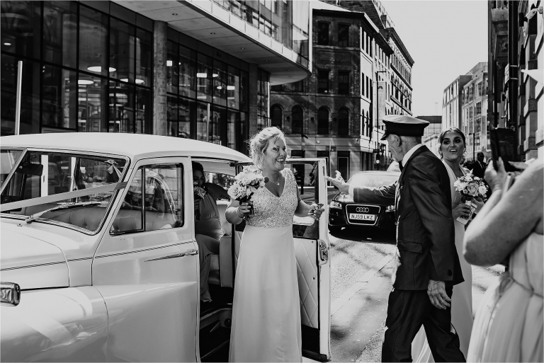 Bridesmaid getting out of the wedding car outside King Street Townhouse