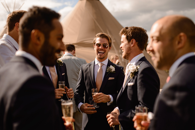 Wedding Guests laughing, photographed through other guests in the foreground